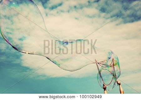 Blowing big soap bubbles in the air. Vintage freedom, summer concepts. Puffy clouds sky.