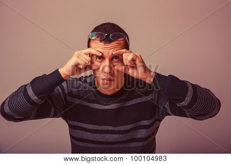 European-looking male of about thirty brunet stretches eyes with