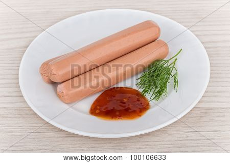 Two Sausages With Dill And Ketchup In Glass Plate