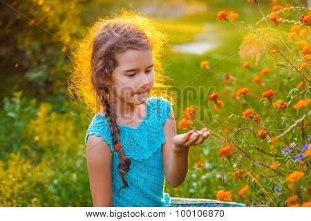 Girl child explores exploring orange flower in nature sunset sum
