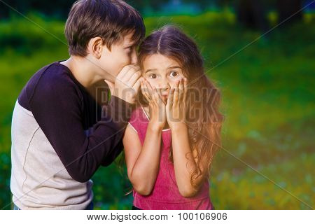 girl whispering in the ear of the boy tells the secret hearings