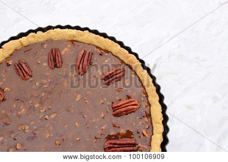 Pecan Nuts Decorating The Top Of An Unbaked Pecan Pie