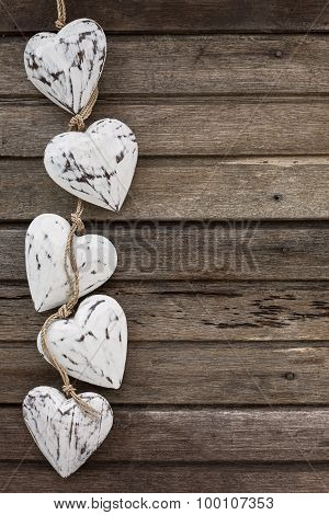 White Wooden Hearts On Old Brown Wooden Background