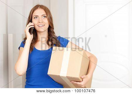 Cheerful woman holding box