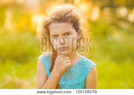 Teenage girl is thinking on a green background on the nature of