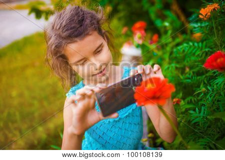 Teenage girl photographing flower phone on a green background in