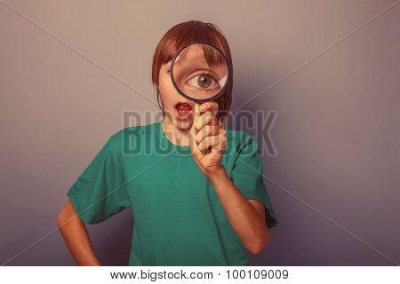 European-looking boy of ten years a joke, looking through a magn