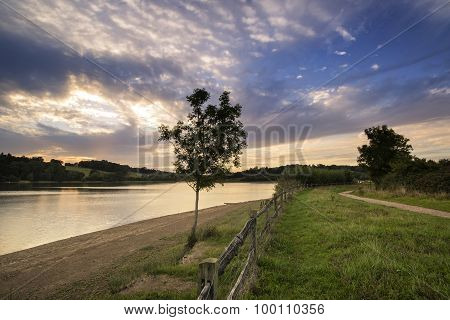 Dramatic Stormy Sunset Over Calm Lake In Summer In English Countryside