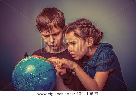 Teenage boy with a girl looking at a globe showing thumbs up on