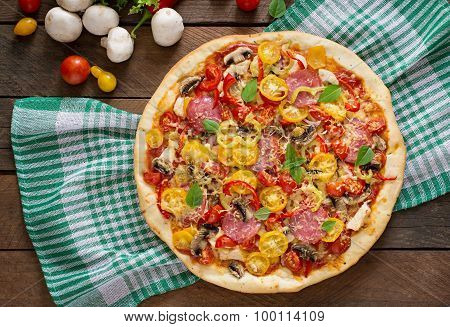 Pizza with salami, tomato, cheese and mushrooms.