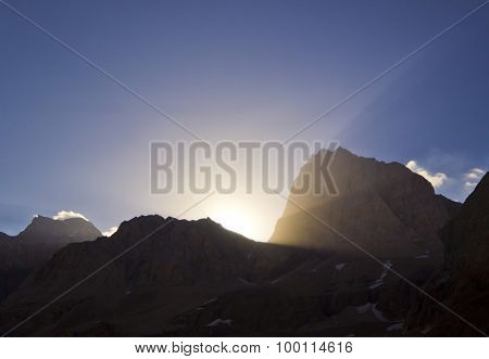yellow sunrise above mountain rocks with sun crown