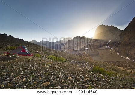 tent in mountains at yellow sunrise above rocks