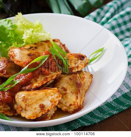 Delicious ravioli with tomato sauce and green onions