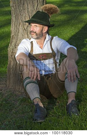 Man In Traditional Bavarian Clothes Sitting By A Tree