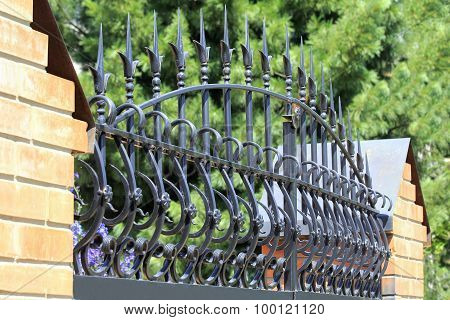 Forged Fence Gate On Against A Park