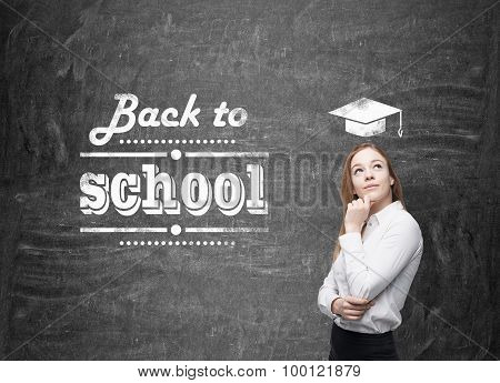 Young Schoolgirl Is Thinking About Future Academic Year. Words: ' Back To School ' Are Written On Th