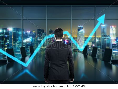 Rear View Of The Businessman In The Office At Night Time. Rising Arrow As A Symbol Of The Success.