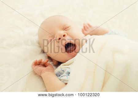 Sweet Sleep Infant Lying And Yawning On The Bed At Home