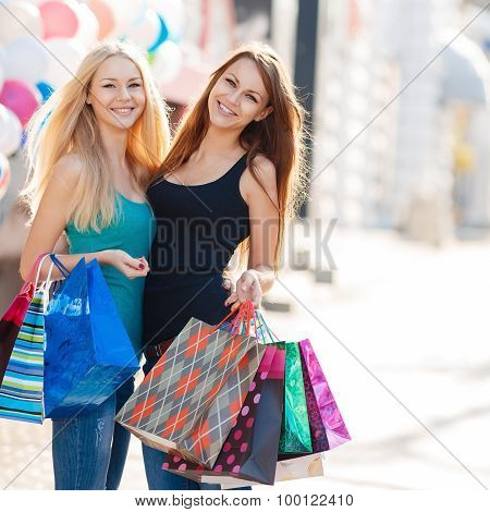 Two beautiful girls with colorful shopping bags - shopping in the big city