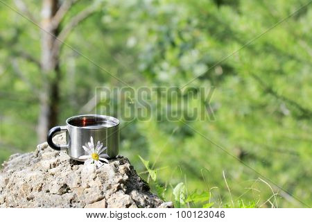 Metal Mug With Red Tea Stands On A Rock Above The Trees