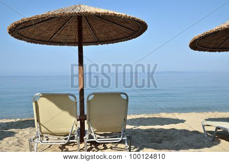 Beach Straw Parasols And Pair Of Chairs