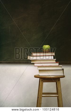 Pile of books and apple on stool with vintage feel