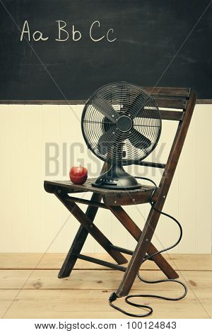 Old fan with apple on chair in school room