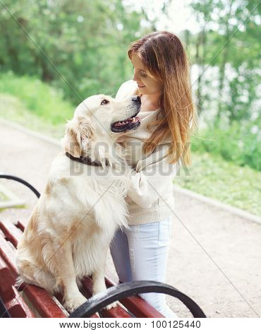Happy Owner Woman And Golden Retriever Dog Sitting On The Bench In City Park