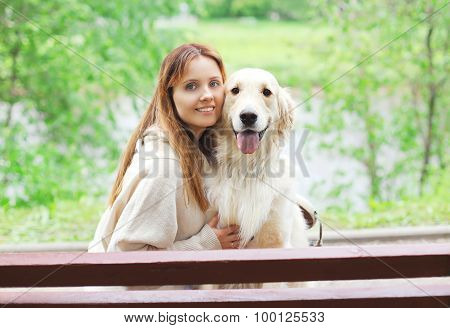 Portrait Of Happy Owner Woman And Golden Retriever Dog Sitting Together On The Bench In City Park