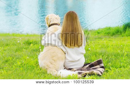 Silhouette Of Owner And Golden Retriever Dog Sitting Together On The Grass Near River In Sunny Summe