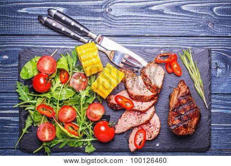 Bbq Lamb Steak With Vegetable Salad And Corn On Dark Wooden Background.