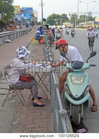 man is going to buy lottery ticket on street in Hanoi, Vietnam