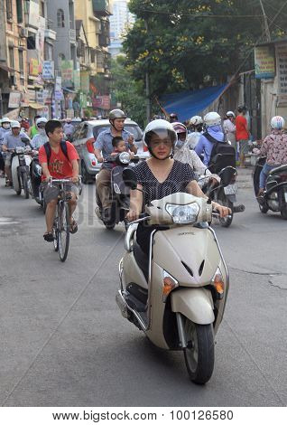 people are riding on motorcycles in Hanoi, Vietnam