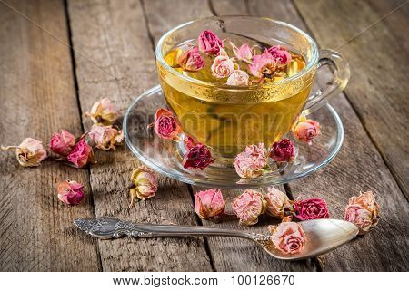 Cup of green tea with dried roses
