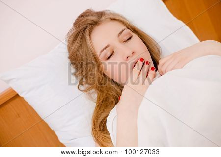 Young beautiful woman with closed lying in bed yawning