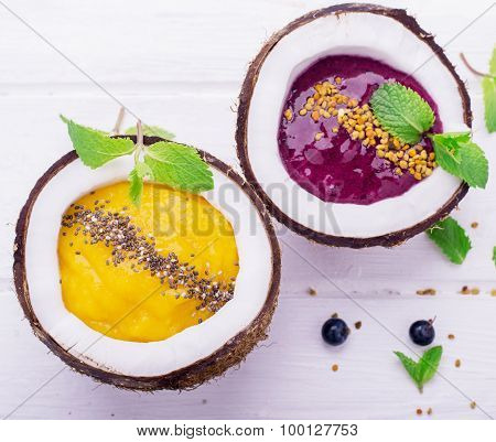 healthy breakfast smoothie mango and berries garnished with chia seeds, bee pollen