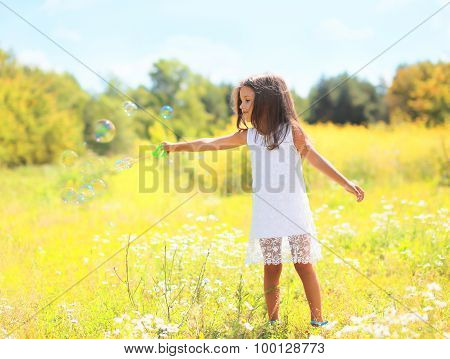 Child Playing Blowing Soap Bubbles On Meadow In Sunny Summer Day