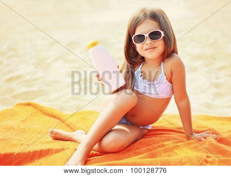 Child Sitting On The Beach And Showing Sunscreen Skin
