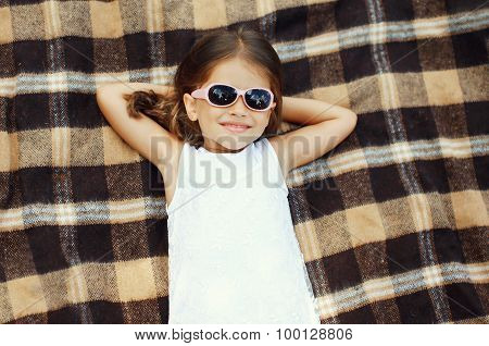 Happy Little Girl Child In Sunglasses Lying Resting On The Plaid, Top View