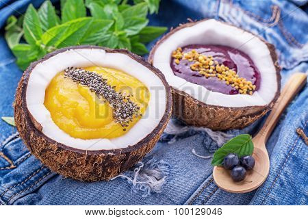 Breakfast mango and berry smoothies garnished with chia seeds, bee pollen in coconut