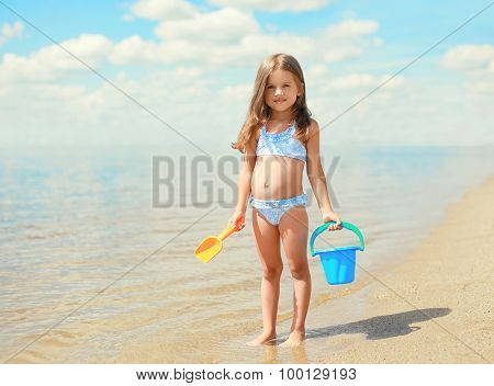 Little Girl Child With Toys Playing And Having Fun On The Beach Near Sea In Summer Sunny Day