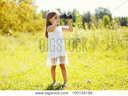 Little Girl Looks In Binoculars Outdoors In Summer Day