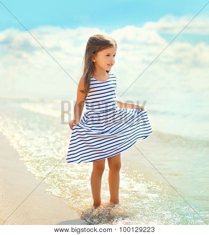 Portrait Of Beautiful Little Girl Child In A Striped Dress Walking On The Beach Near Sea With Waves,