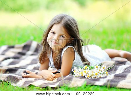 Portrait Of Beautiful Little Girl Child With Chamomiles Flowers Lying On The Plaid Outdoors