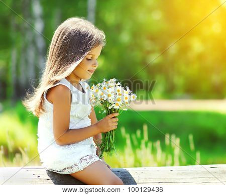 Portrait Of Cute Little Girl Child With Bouquet Of Chamomiles Flowers In Sunny Summer Day