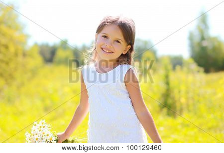 Portrait Of Cute Smiling Little Girl Child With Bouquet Of Chamomiles Flowers In Summer Day