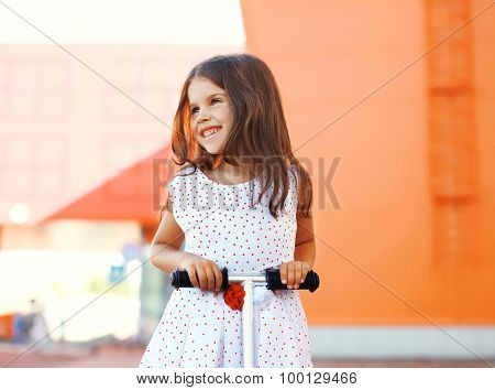 Portrait Of Happy Smiling Little Girl On The Scooter Having Fun Outdoors