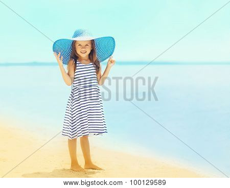 Summer, Vacation, Travel And People Concept - Beautiful Little Girl In A Striped Dress And Summer St