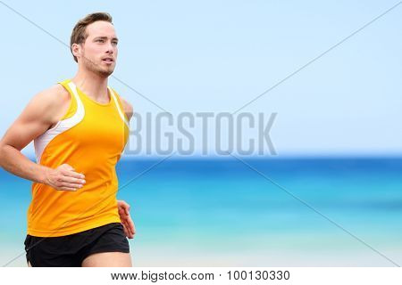 Handsome fit Running young man jogging on shore. He is in sports clothing. Determined male jogger is exercising at beach.