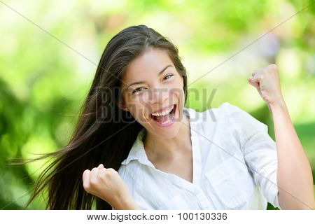 Portrait of successful young woman with clenched fists. Attractive female is celebrating victory. She is in casuals at park.